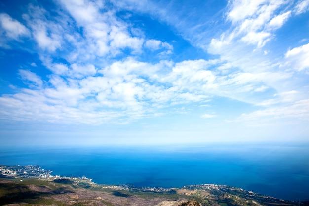 Фото с вершины горы ай-петри, дерево растет на скале, красивый горизонт и голубое небо с белыми облаками.