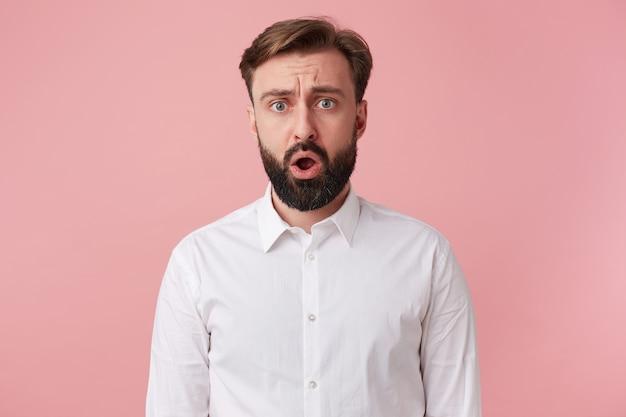 Foto di cipiglio attraente uomo barbuto stordito, indossa una camicia bianca. guardando la telecamera con la bocca spalancata isolata su sfondo rosa.