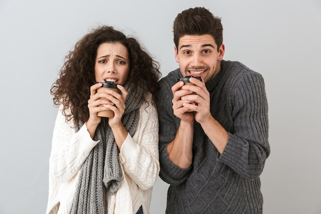 Photo of frozen couple man and woman wearing scarfs trembling and holding cups with hot tea or coffee, isolated over gray wall