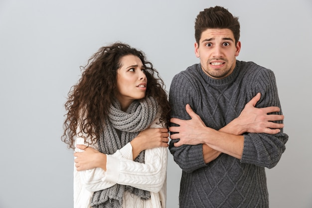 Photo of frozen couple man and woman wearing scarfs trembling and hugging themselves, isolated over gray wall