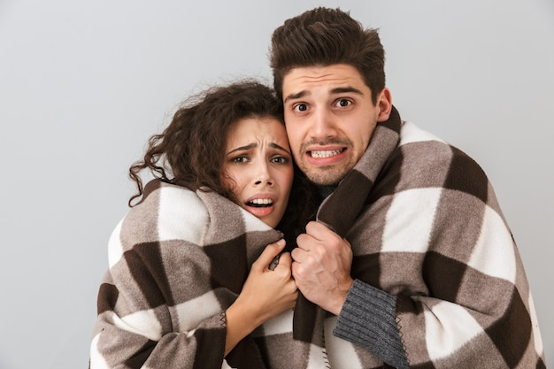 Photo of frozen couple man and woman wrapped in blanket trembling and hugging together, isolated over gray wall