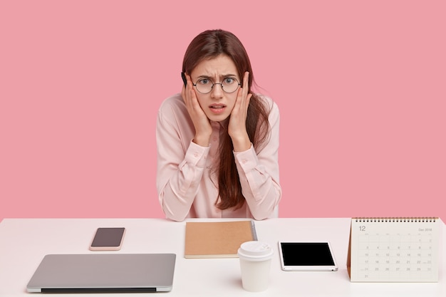 Photo of frustrated caucasian woman dressed in elegant shirt, poses at workplace alone, has neatly arranged things, wears round spectacles