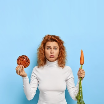 Photo of frustrated disappointed young woman keeps to diet, purses lower lip, makes hard choice between bun and carrot, healthy nutrition and junk food, has curly red hair, appealing appearance
