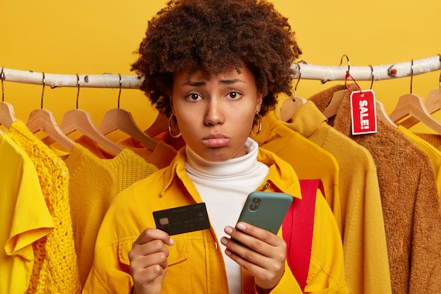 Photo of frustrated female buyer visits clothes shop, uses mobile phone and credit card for online payment, stands against yellow background