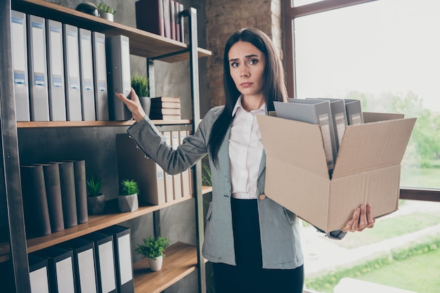 Photo of frustrated girl marketer lawyer attorney lose company covid corona virus economics crisis collect folders hold cardboard box wear suit blazer jacket in loft office