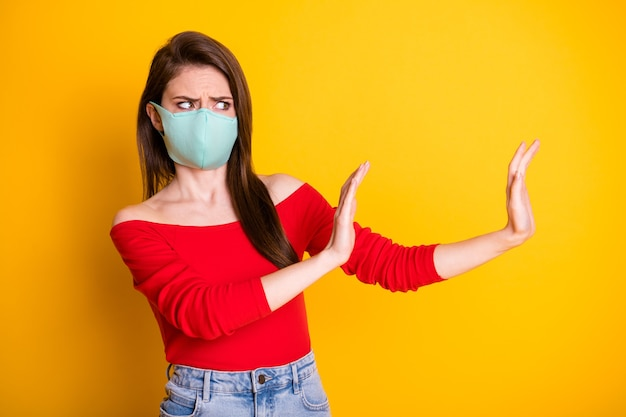 Photo of frustrated girl in medical mask hold hand copyspace stop spread covid infection epidemic ill wear red top denim jeans isolated over bright shine color background