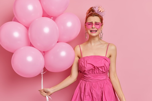 Photo of frustrated redhead woman cries from despair poses in festive clothing with bunch of inflated balloons isolated over pink wall. bad holiday concept. this party sucks. human emotions