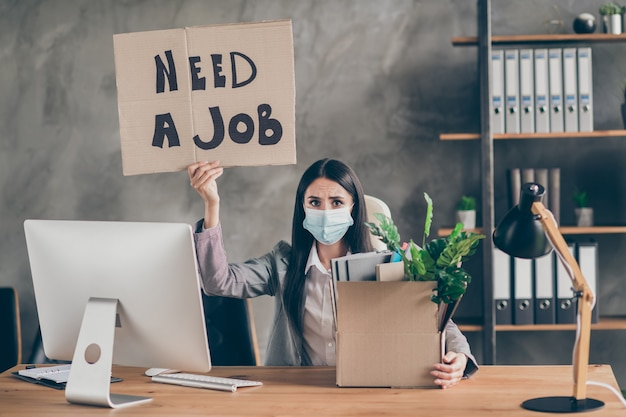 Photo of frustrated sad upset girl with medical mask sit desk table lost job corona virus quarantine company bankrupt crisis hold cardboard text  box in workplace workstation
