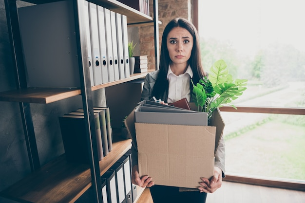 Photo of frustrated stressed depressed girl ceo expert lose job hold cardboard box with folders wear blazer jacket suit in workplace workstation