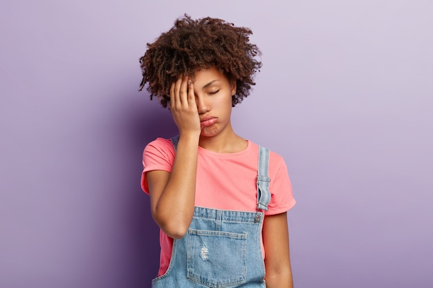 Photo of frustrated tired dark skinned woman covers face with palm, feels overworked, prepared for exam all night, has sleepy expression, dressed in stylish clothing, models over violet wall