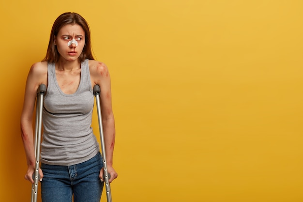 Photo of frustrated unhappy female victim of road accident, turns gaze aside, walks on crutches, has plaster on broken nose, poses against yellow wall, copy space aside. health problems