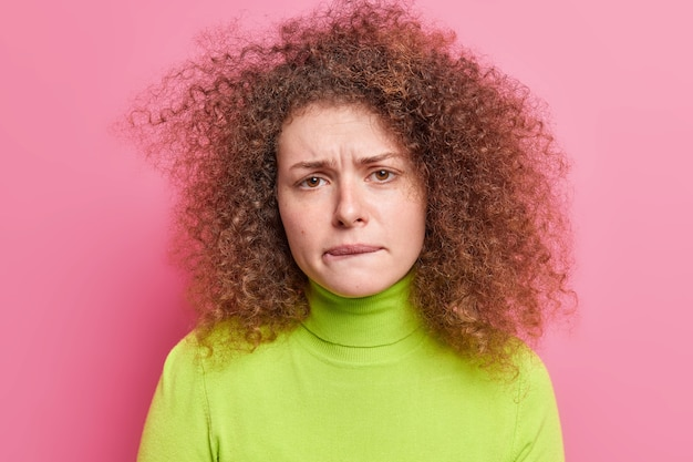 Photo of frustrated unhappy woman with curly hair bites lips looks nervously  feels anxious dressed in casual green turtleneck isolated over pink wall. perplexed troubled female