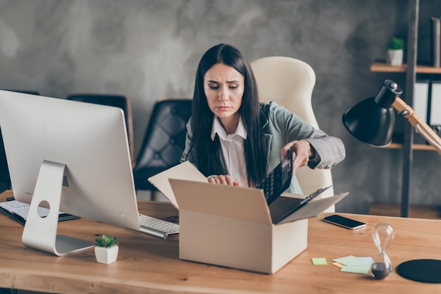 Photo of frustrated upset girl agent collar representative collect her belongings lost job quarantine company crisis sit desk table in workplace workstation office