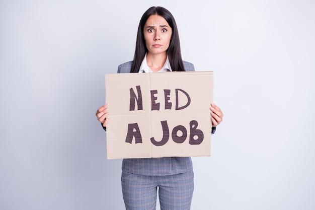 Фото разочарованная женщина агент экономист сотрудники компании свободная работа держать бумажную карточку текст нужно работать последняя надежда носить клетчатые клетчатые брюки брюки куртка изолированный серый цвет фона