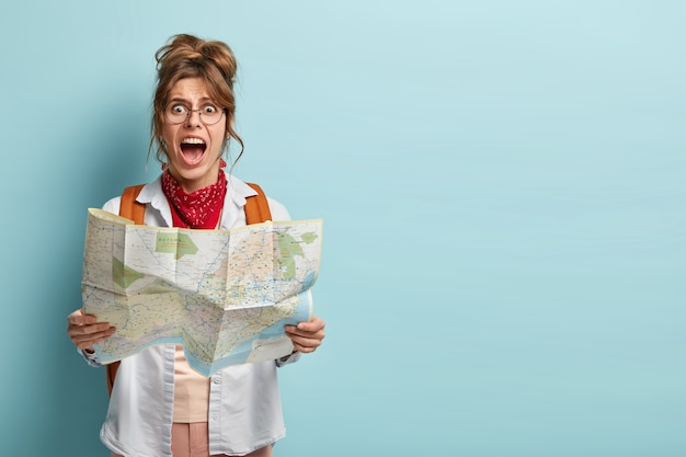 Photo of frustrated woman traveler lost in city, looks depressed at paper map, shouts from despair