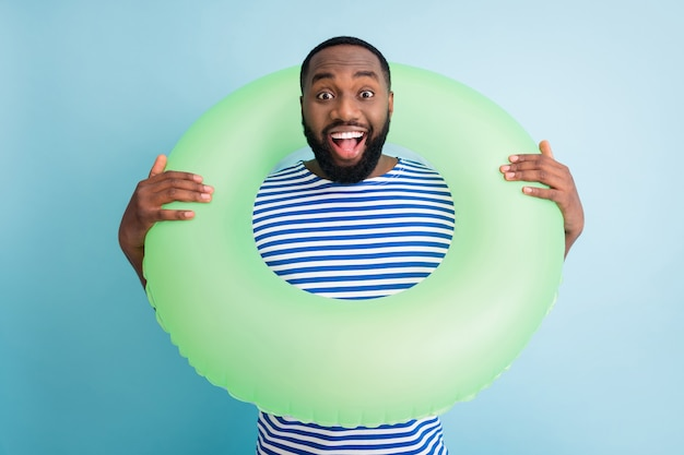Photo of funky dark skin guy hold green life buoy ready swim ocean sea traveler see sale banner advert enjoy shopping rest abroad wear striped sailor shirt isolated blue color wall