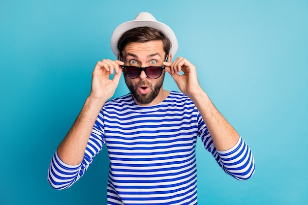 Photo of funky excited handsome guy tourist taking off cool black sun specs open mouth read discounts banner wear striped sailor shirt cap isolated blue color