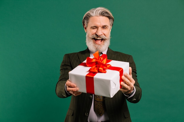 Photo of funky mature guy amour in khaki suit cupid character role showing big gift box on a valentine day isolated green color background