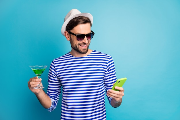 Photo of funky traveler guy browsing telephone drink green alcohol cocktail all inclusive exotic resort wear sun specs striped sailor shirt cap isolated blue color