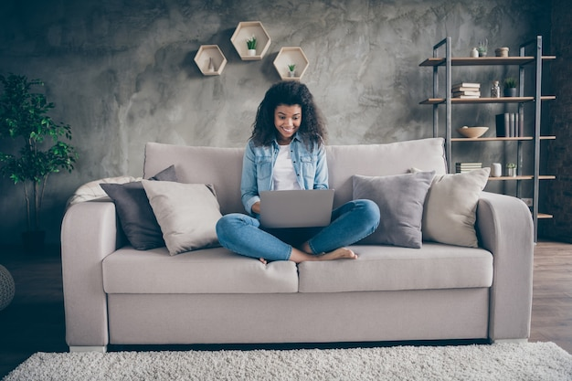 Photo of funny amazed dark skin wavy lady notebook on knees crossed legs texting friends read good news sitting cozy couch casual denim outfit living room indoors