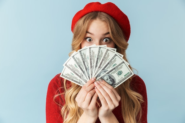 Photo of funny blond woman 20s wearing red beret holding bunch of money banknotes isolated