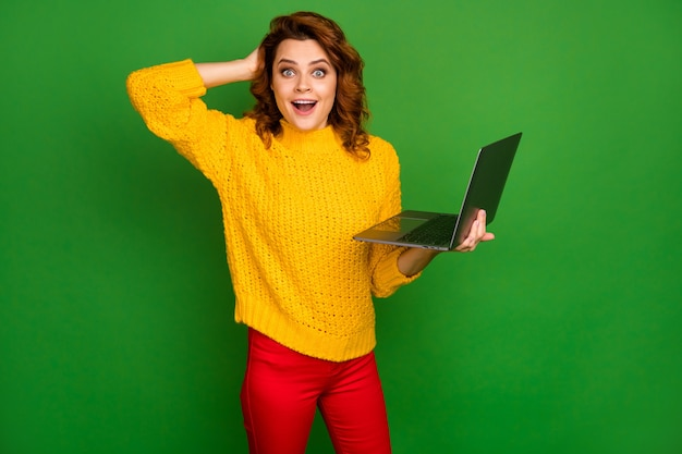 Photo of funny business lady administrator hold notebook hands browsing it website arm on head read cool good news wear yellow knitted pullover red pants isolated green color wall