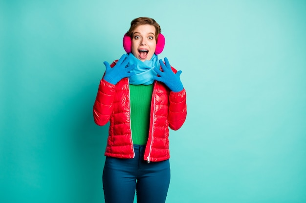 Photo of funny crazy lady holding hands near face excited feelings christmas surprise wear casual red overcoat blue scarf pink ear covers jumper pants isolated teal color wall