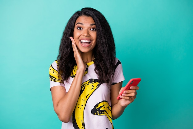 Photo of funny cute girl hold telephone arm cheekbone look camera wear banana print t-shirt isolated teal color background