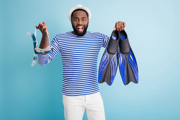 Photo of funny dark skin guy hold diver devices flippers tube goggles mask excited to start sinking wear white sun cap striped sailor shirt shorts isolated blue color wall