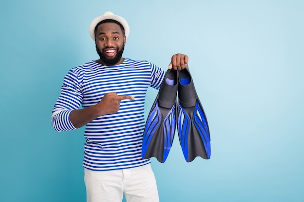 Photo of funny dark skin guy hold diver flippers excited to start sinking direct finger best mark model fins wear white sun cap striped sailor shirt shorts isolated blue color wall