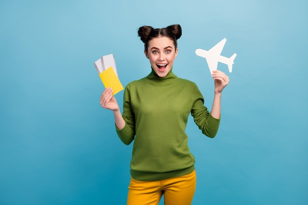 Photo of funny excited lady hold paper air plane passport tickets addicted traveler buy cheap tour abroad wear green turtleneck yellow trousers isolated blue color wall