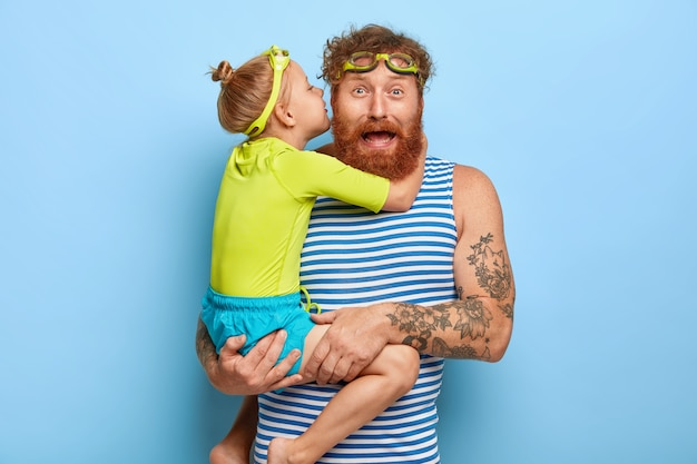 Photo of funny ginger father receives hug and kiss from small daughter, carries child on hands, wear swim goggles, spend free time at swimming pool, wear casual clothing, have good relationship