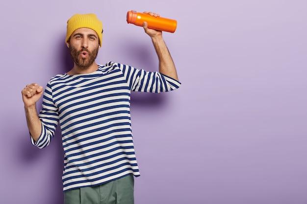 Foto di un ragazzo divertente hipster balla e canta, essendo di buon umore trasporta thermos arancione con bevanda calda