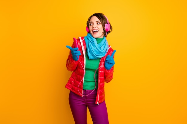 Photo of funny lady hold telephone listen earphones dancing excited party chilling mood wear casual red coat blue scarf gloves trousers