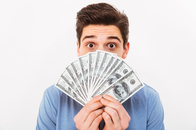 Photo of funny man in casual t-shirt covering his face with fan of money in dollar currency, isolated over white wall