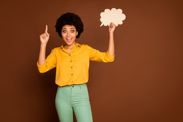 Photo of funny pretty dark skin curly lady hold empty paper cloud banner poster have creative dialogue answer idea wear yellow shirt green pants isolated brown color