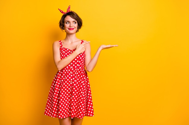 Photo of funny pretty lady hold open arm product indicating finger presenting cool novelty wear retro style summer dotted red white dress headband isolated yellow color wall