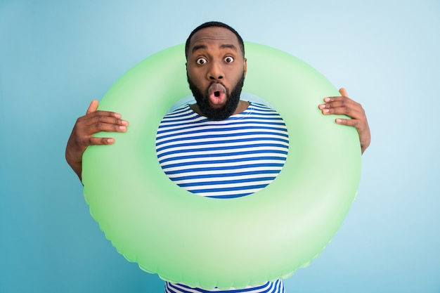 Photo of funny speechless dark skin guy hold green life buoy ready swim ocean sea traveler see sale banner advert not believe eyes wear striped sailor shirt isolated blue color wall