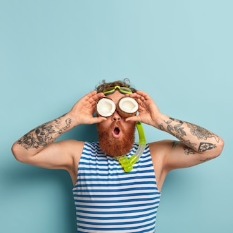 Photo of funny surprised guy covers eyes with coconuts, has thick ginger beard