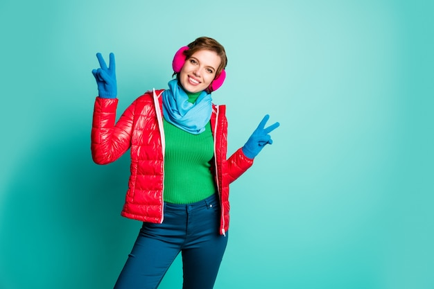 Photo of funny traveler lady enjoy sunny winter day rejoicing showing v-sign symbol skating wear casual red overcoat blue scarf pink ear covers trousers isolated teal color wall