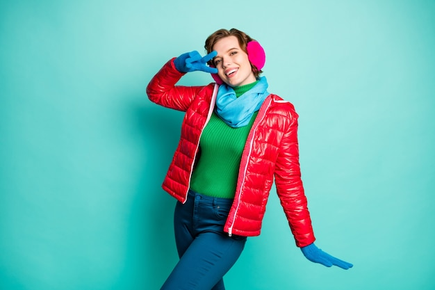 Photo of funny traveler lady enjoy sunny winter day rejoicing showing v-sign symbol wear stylish casual red overcoat blue scarf pink ear warmers trousers isolated teal color wall