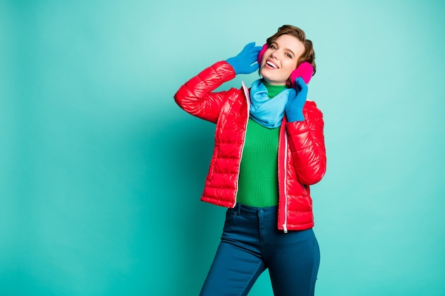 Photo of funny traveler lady enjoy sunny winter day skating spend free time rejoicing wear stylish casual red overcoat blue scarf pink ear covers trousers isolated teal color wall