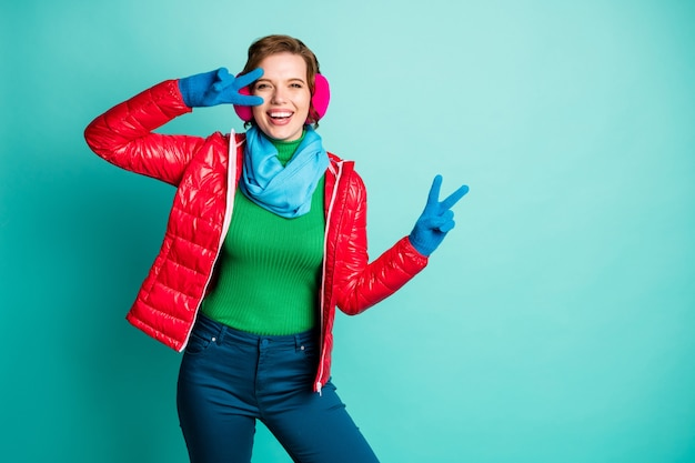 Photo of funny traveler lady enjoy winter day rejoicing showing v-sign symbol skating rink wear casual red overcoat blue scarf pink ear covers trousers isolated teal color wall
