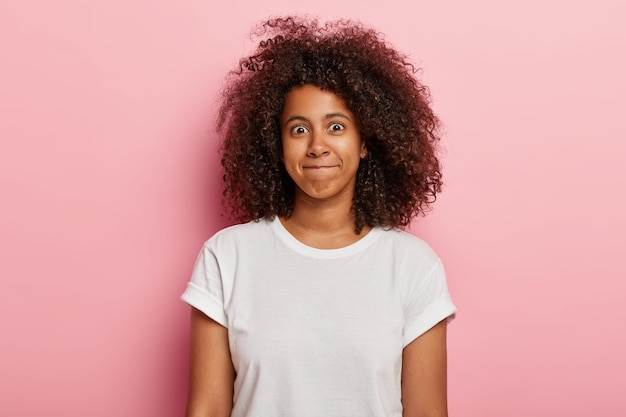 Photo of funny woman has curly thick hair, presses lips together, has happy face, wears white t shirt, isolated over pink wall. good looking young african american girl expresses happiness.