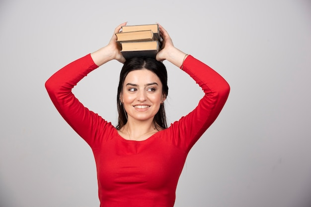 Photo of a funny woman holding books overhead.
