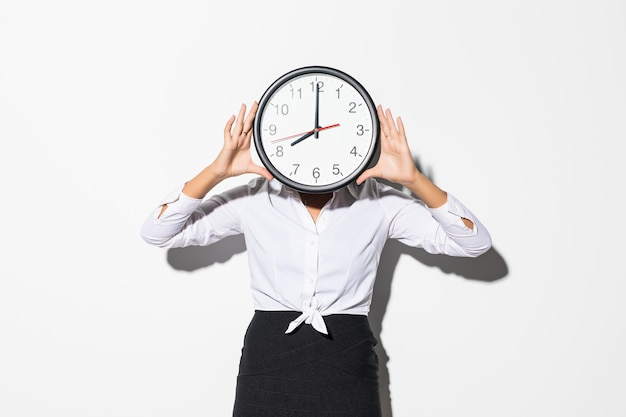 Photo of funny woman in on white shirt and black skirt coning face with big round clock isolated on white