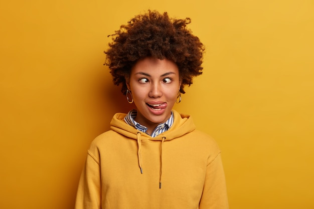 Photo of funny young woman has crazy face, crosses fingers and sticks out tongue, foolishes around, wears casual sweatshirt, poses against yellow wall. comic facial expressions concept