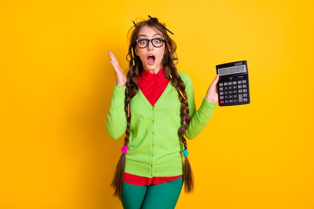 Photo of geek girl with messy hairdo hold calculator astonished isolated bright color background