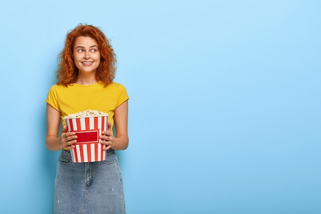 Photo of ginger charming girl holds bucket with popcorn