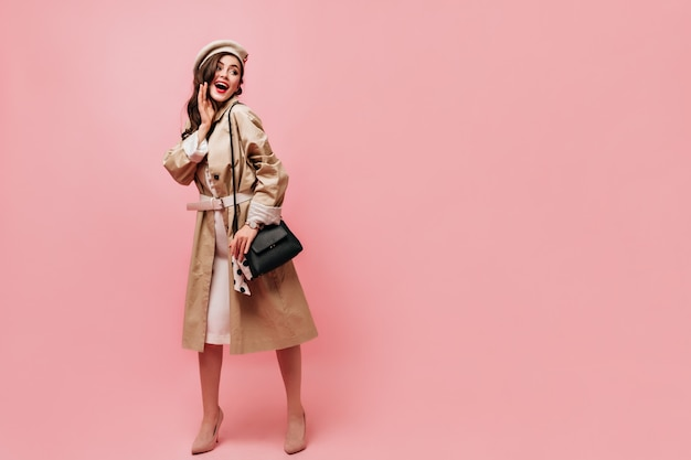 Photo of girl dressed in light trench coat and felt beret posing with black handbag on isolated background.